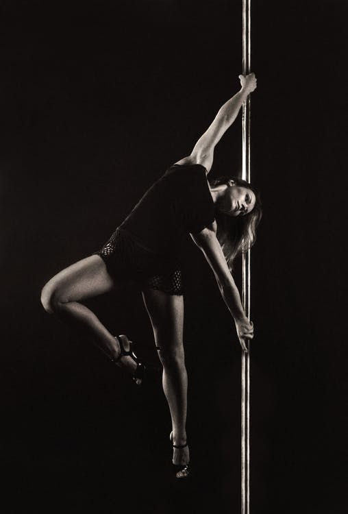 Woman Holding on Dance Pole