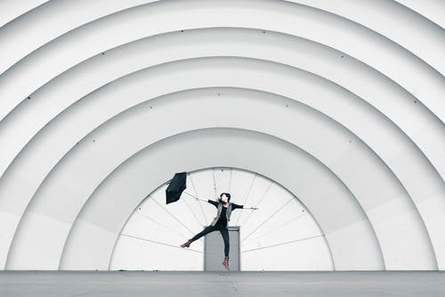 Girl Jumping While Holding Umbrella