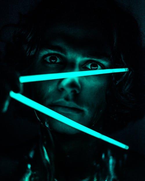 man Holding Neon Light Sticks Inside Dark Room