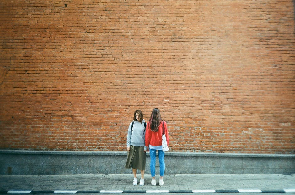 Two women standing beside red brick wall