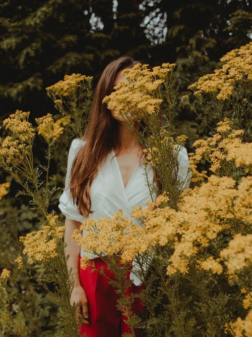 Photo of Woman Standing Near Yellow Petaled Flowers