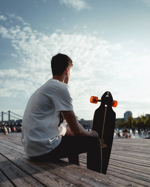 Man Sitting on Brown Wooden Surface Holding Longboard
