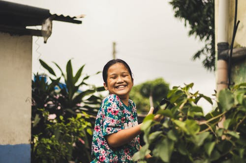 Photo of Smiling Girl with Her Eyes Closed Standing Next to Green-leafed Plants