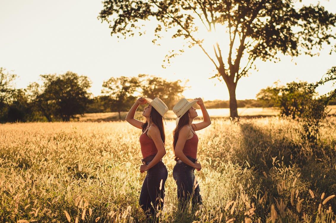 Dos Mujeres De Pie Sobre El Campo De Hierba
