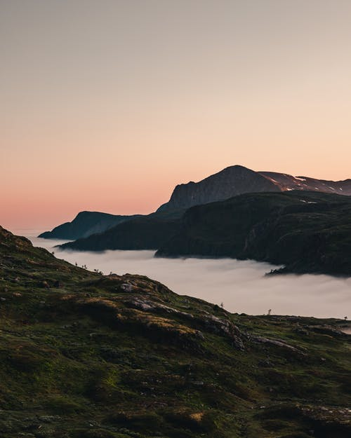 Mountain and hills with dense fog in hollow at sunset