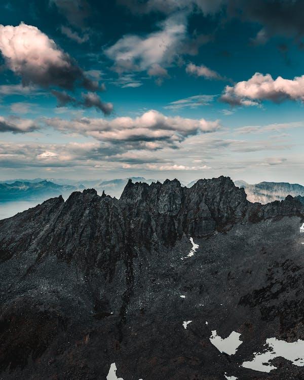 Mountainous terrain with high peaks under blue sky