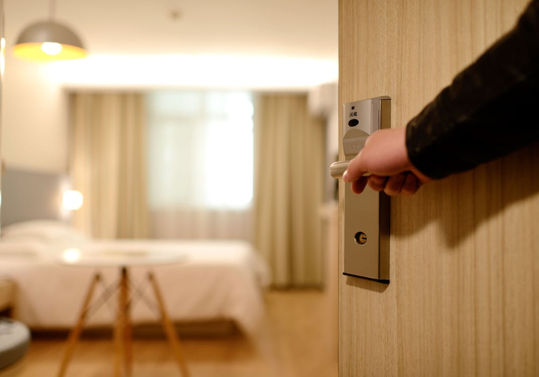 Person Holding on Door Lever Inside Room