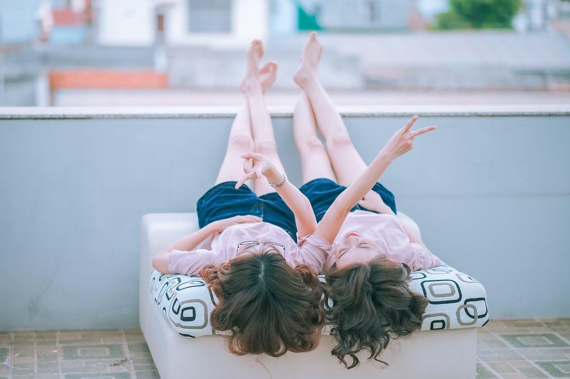 Two Women Lying on White Mattress