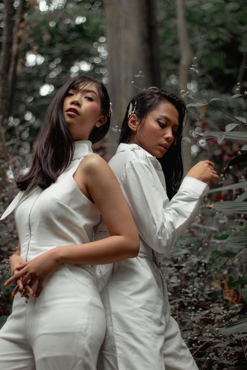 Two Women Wearing White Jumpsuits