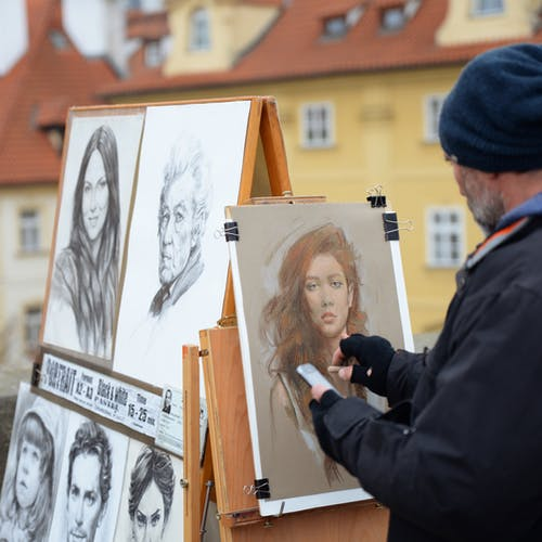 Photo of Man Drawing a Portrait of a Woman