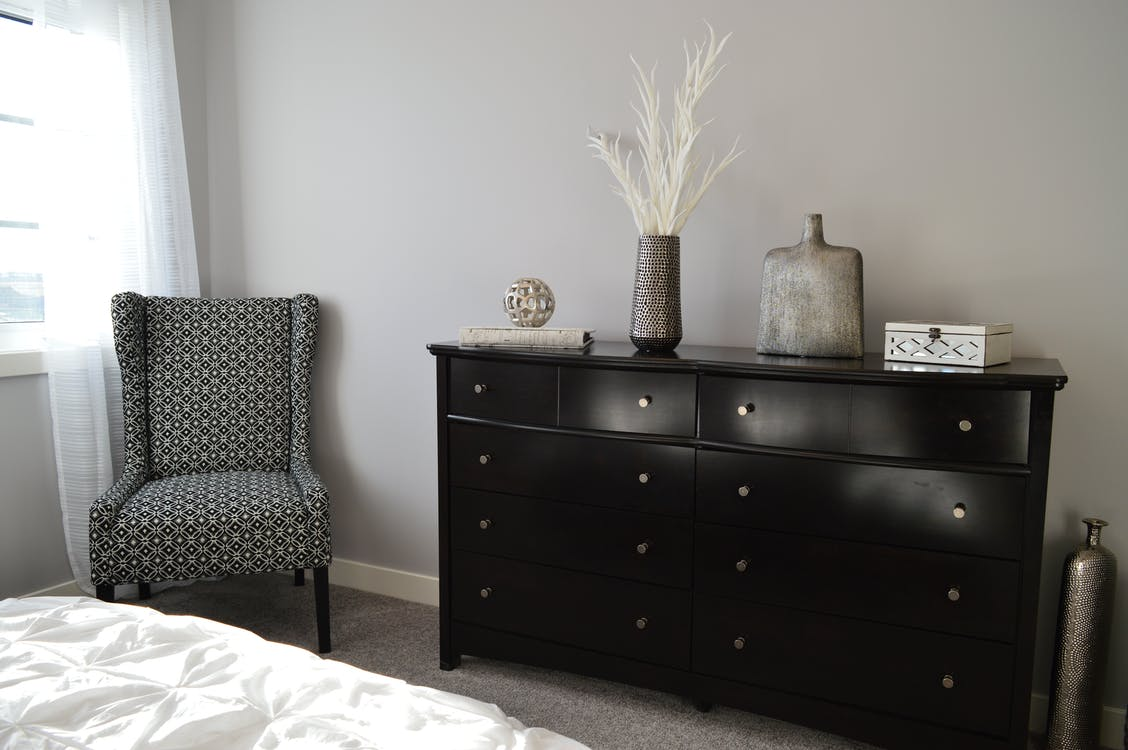 Gray and Black Chair Beside Black Wooden Lowboy Dresser