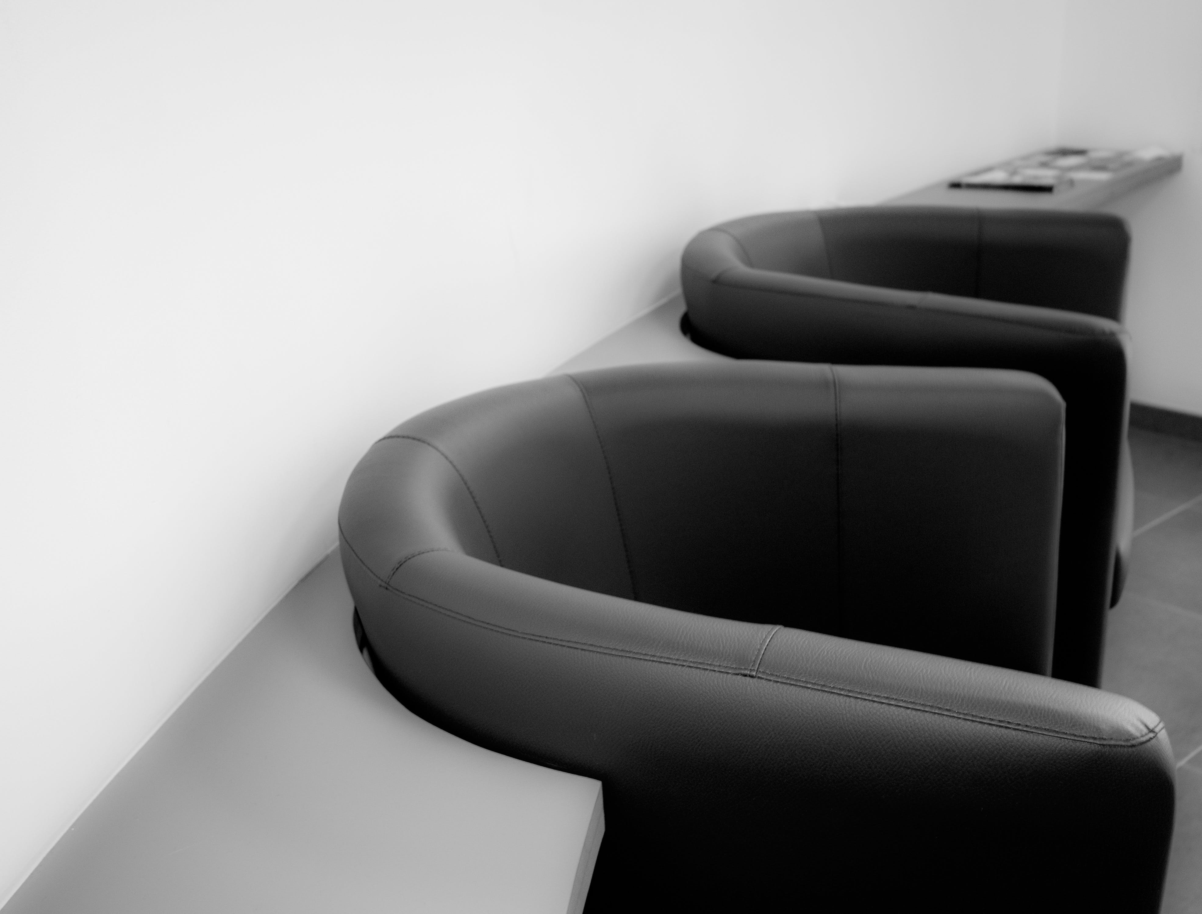 Two Black Leather Tub Chairs