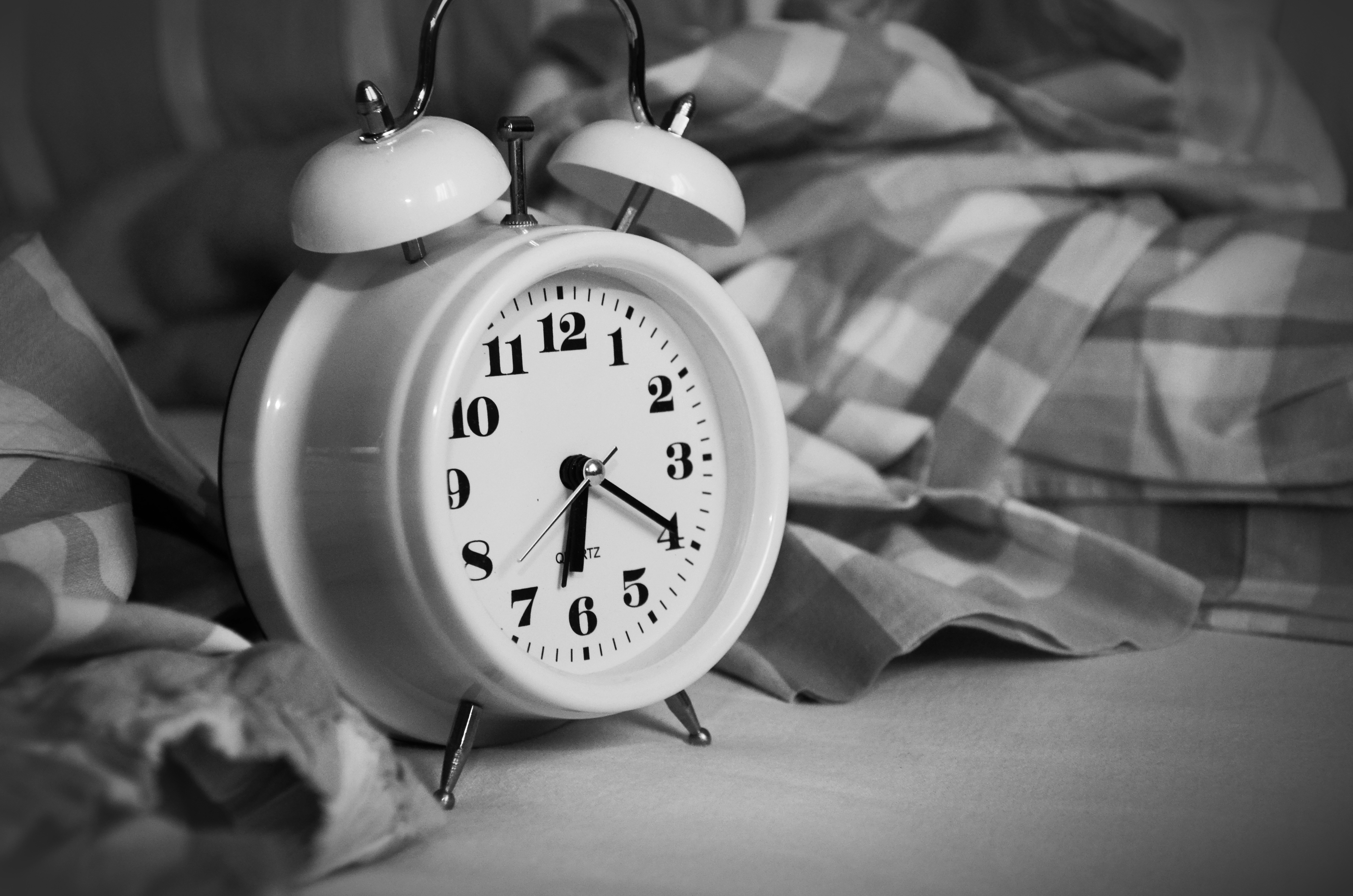 White Alarm Clock on Bed