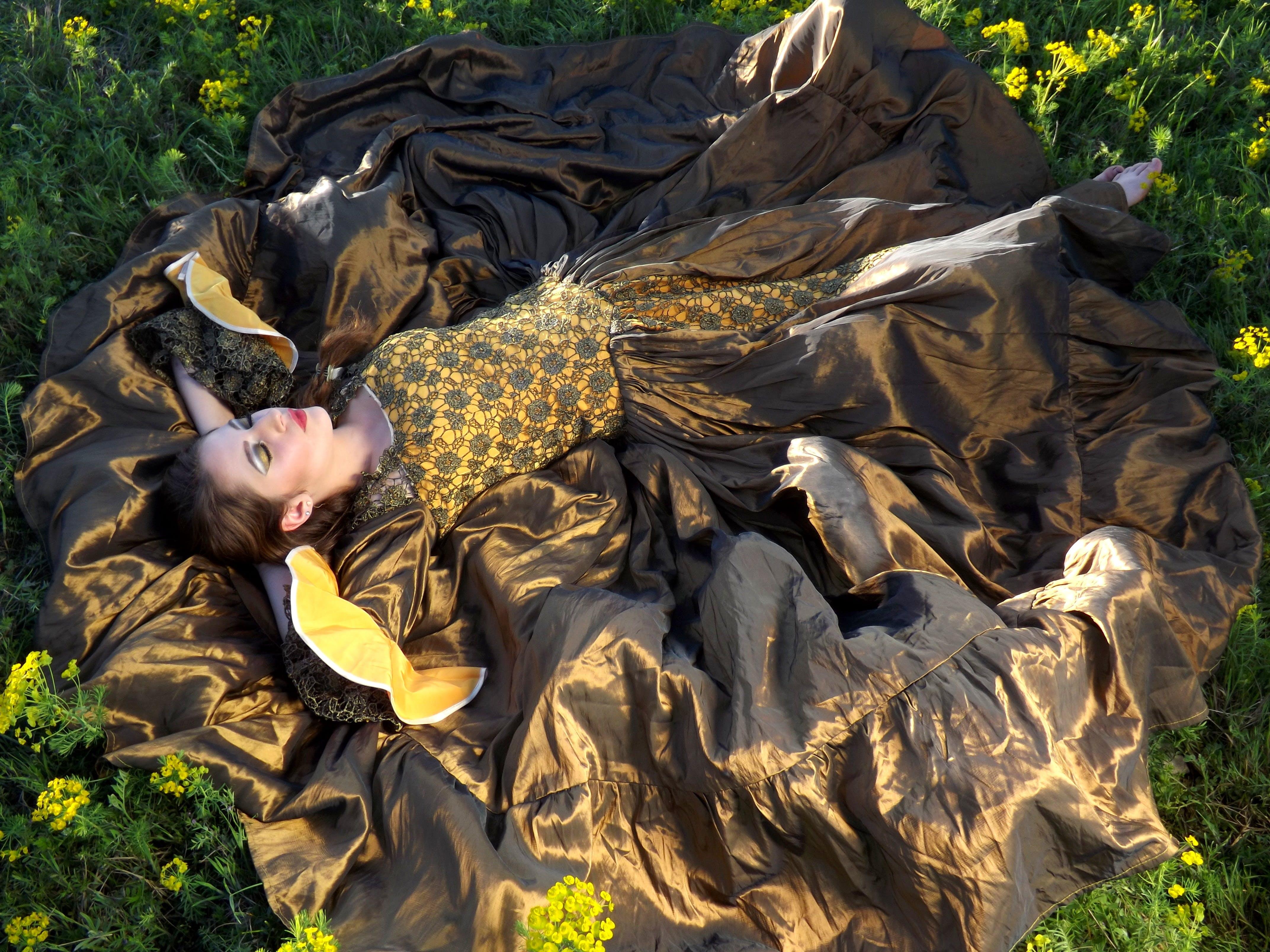 Woman Wearing Black and Yellow Dress Laying on Green Grass