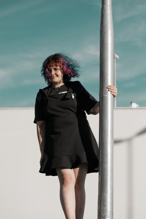 Woman in Black Dress Holding on Pole