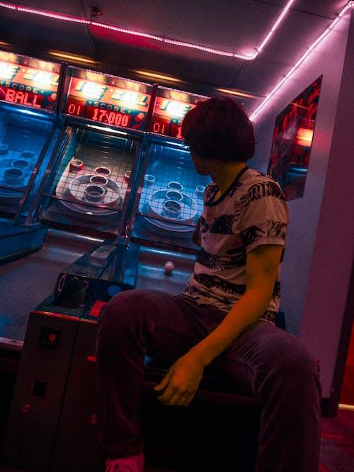Man Sitting on Arcade Basketball Game