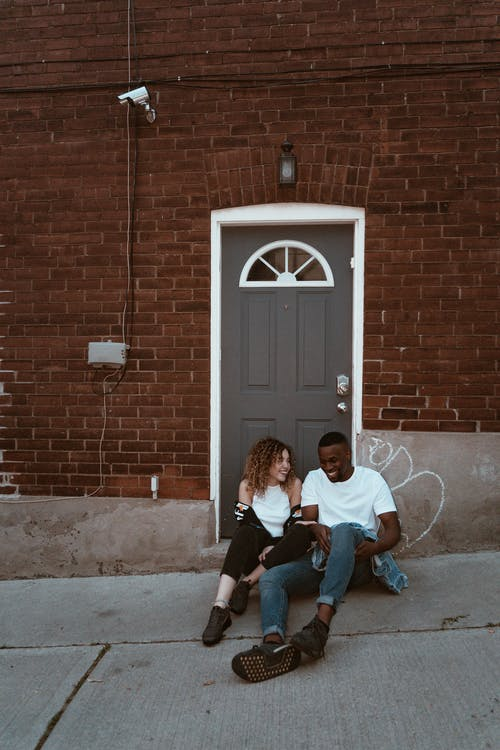 Smiling Man And Woman Sitting Beside Door