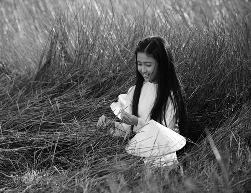 Monochrome Photo of Girl Holding Plant
