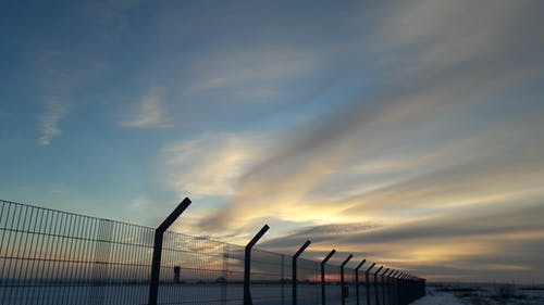 Cumulus Clouds Above Metal Grille Fence