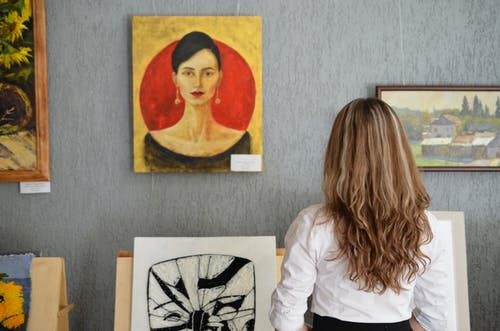 Woman Looking At Paintings Displayed On The Wall