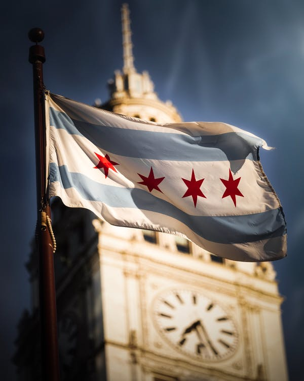 Shallow Focus Photography of Flag of Chicago Near Clock Tower