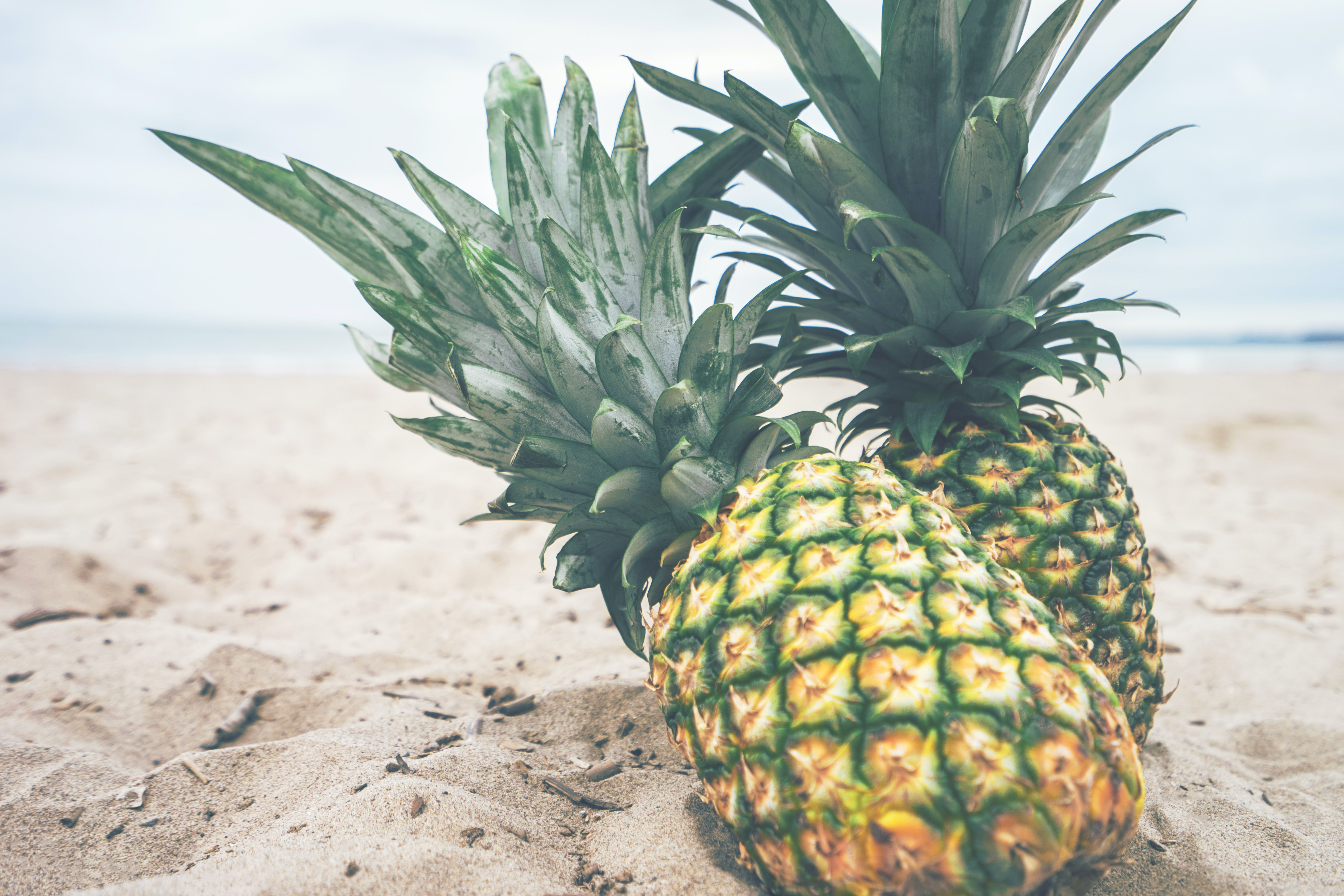 Two Pineapple Fruit on Sad Near Body of Water