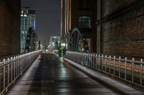 Person Standing Beside Gray Concrete Bridge Near Building