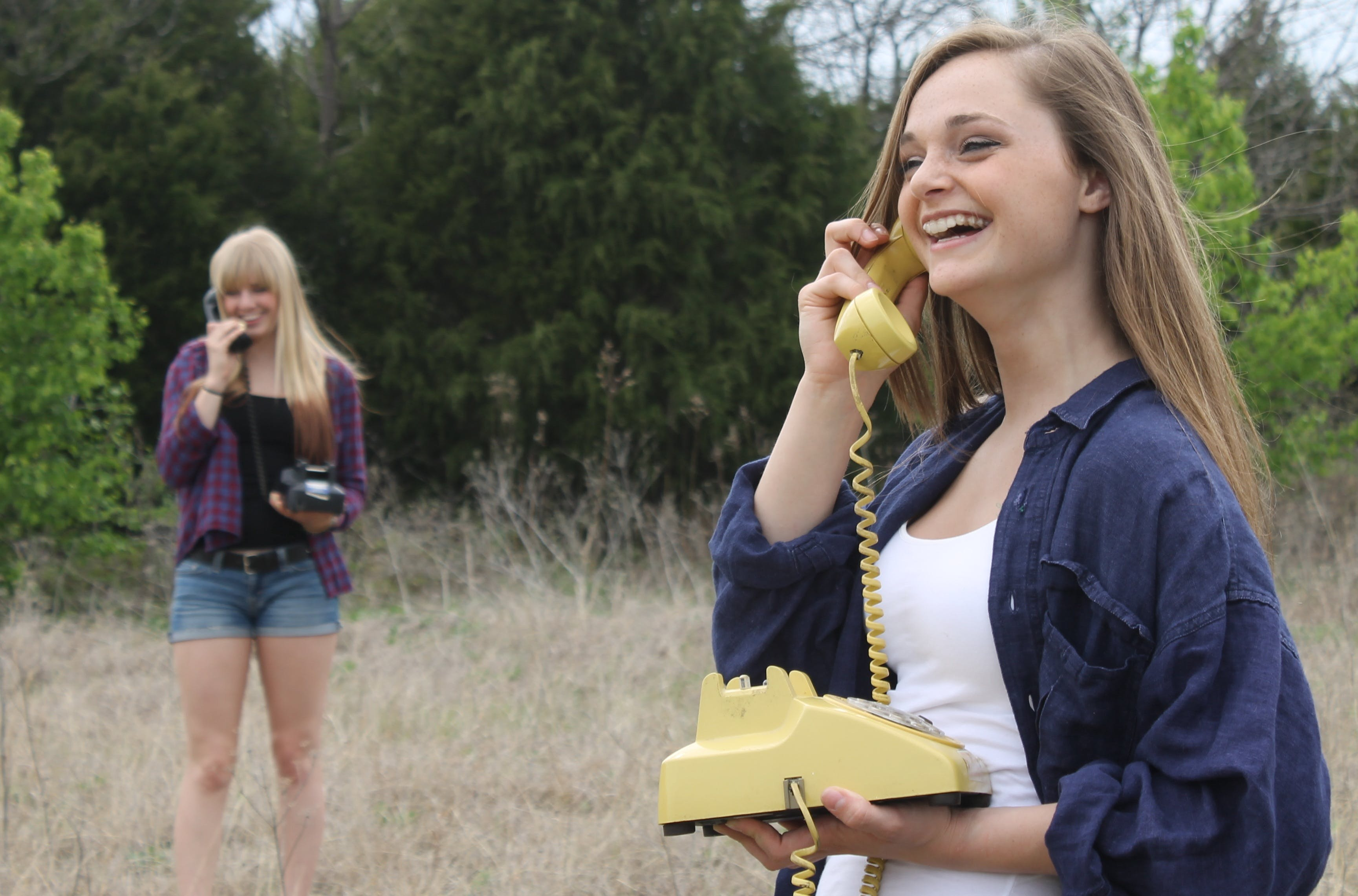 Woman Wearing Blue Denim Button-up Jacket While Using Brown Rotary Phone
