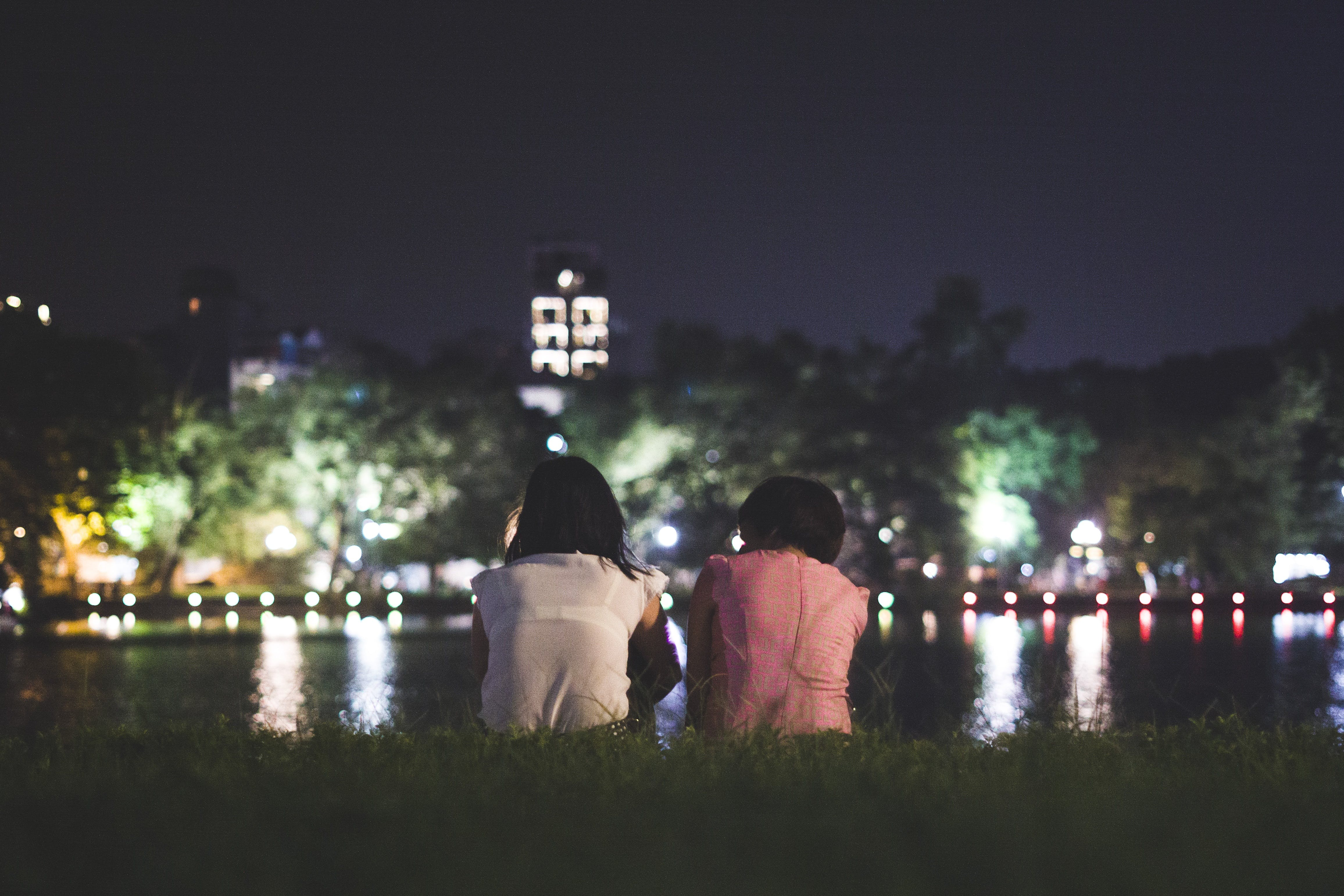 Couple Sitting on Grass in Front of Body of Water