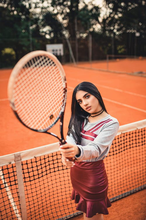 Woman in Grey and Red Long-sleeved Shirt Holding Tennis Racket