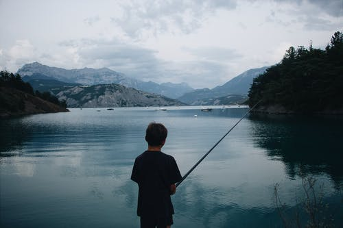 Back view of anonymous boy fishing alone on calm lake surrounded by mountains in cloudy weather