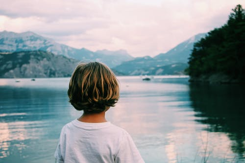 Anonymous kid admiring view on lake along mountains