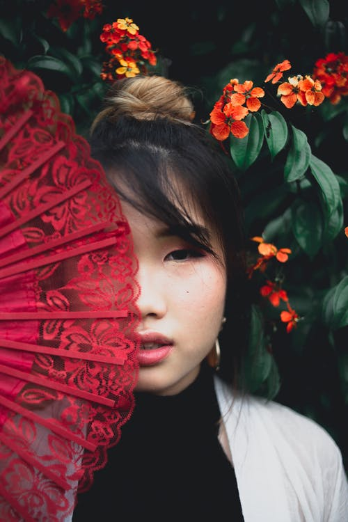 Close-Up Photo of Woman Covering Face With Red Hand Fan