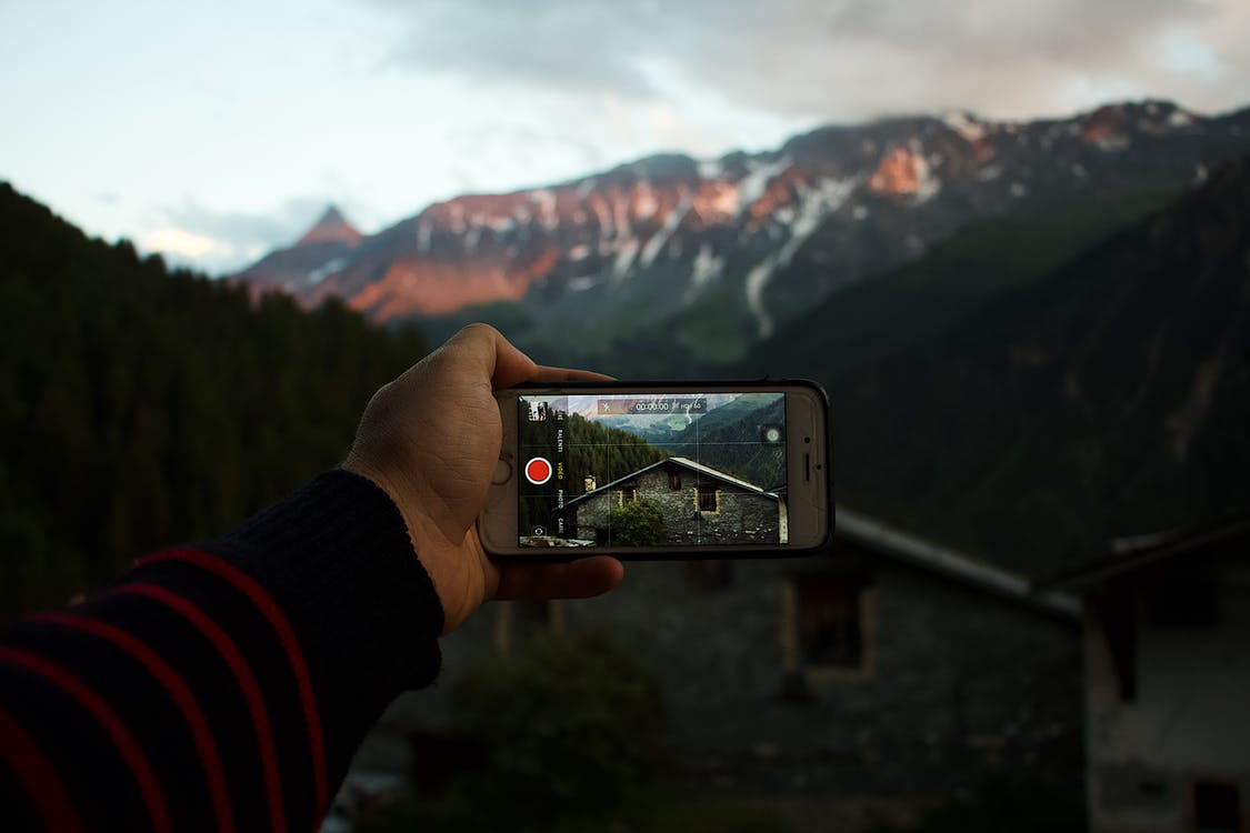 Person Holding Iphone Capturing House and Mountain