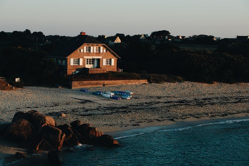 High angle of blue sea and wooden house among green trees on sandy shore during sundown