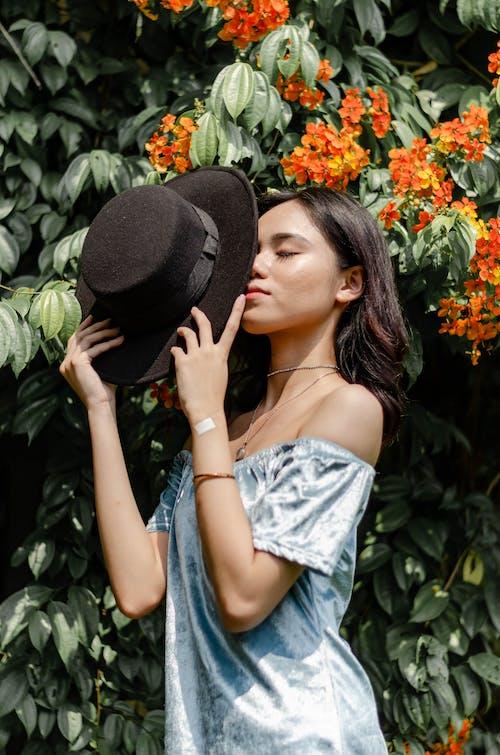 Woman Holding Black Hat Near Orange Flowers
