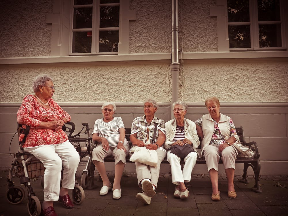 Group of Women Sitting on Bench Outdoors
