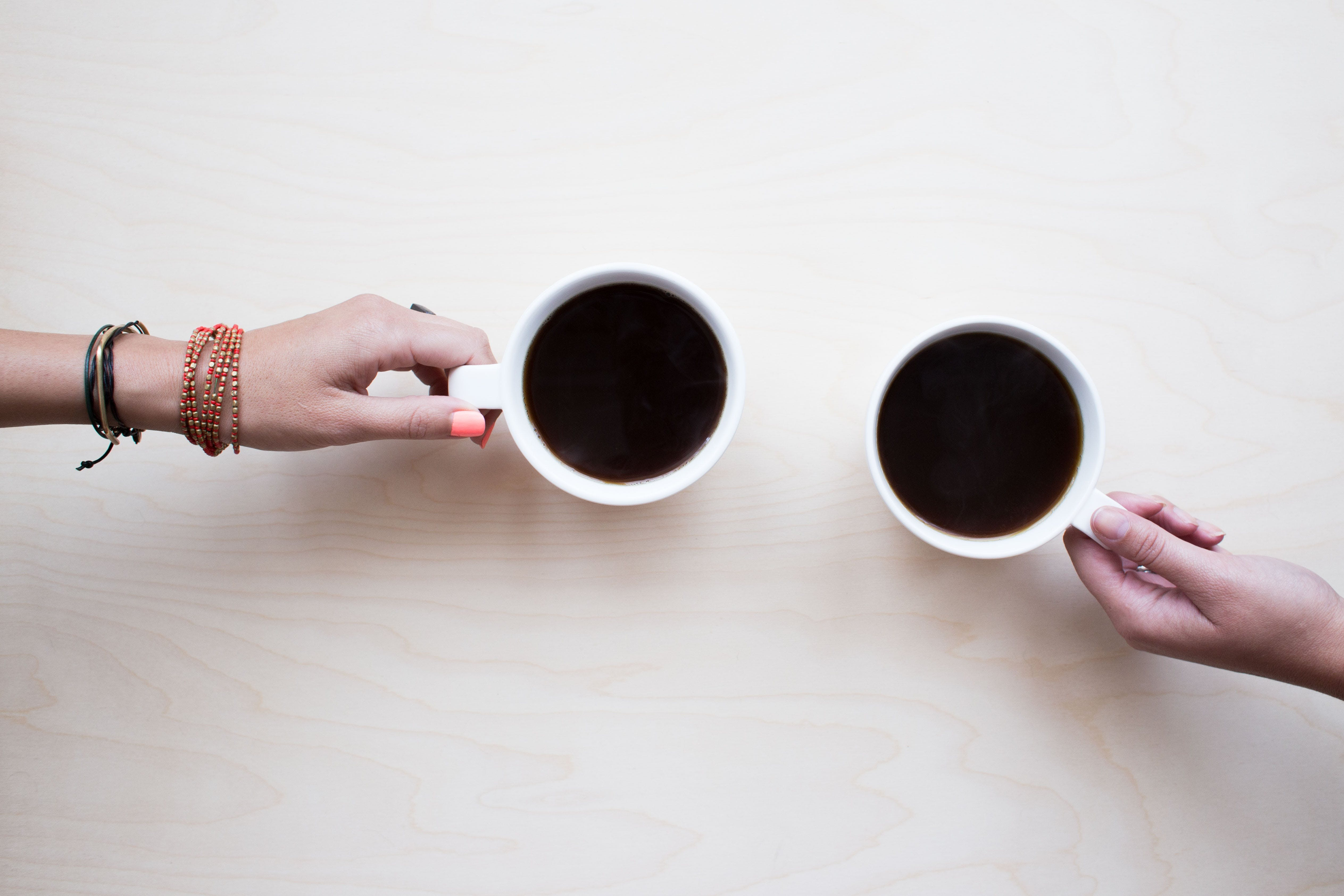 Two People Holding White Mugs