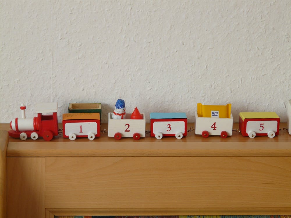 Plastic Toy Train on Wooden Rack