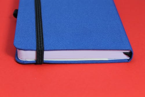 Blue Notebook on Red Surface