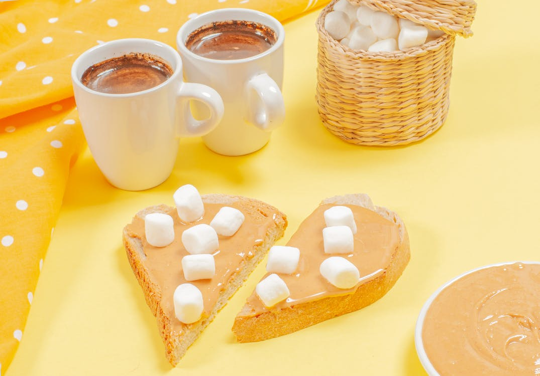 Two Chocolate Drinks Beside Peanut Butter Sandwich With White Marshmallows