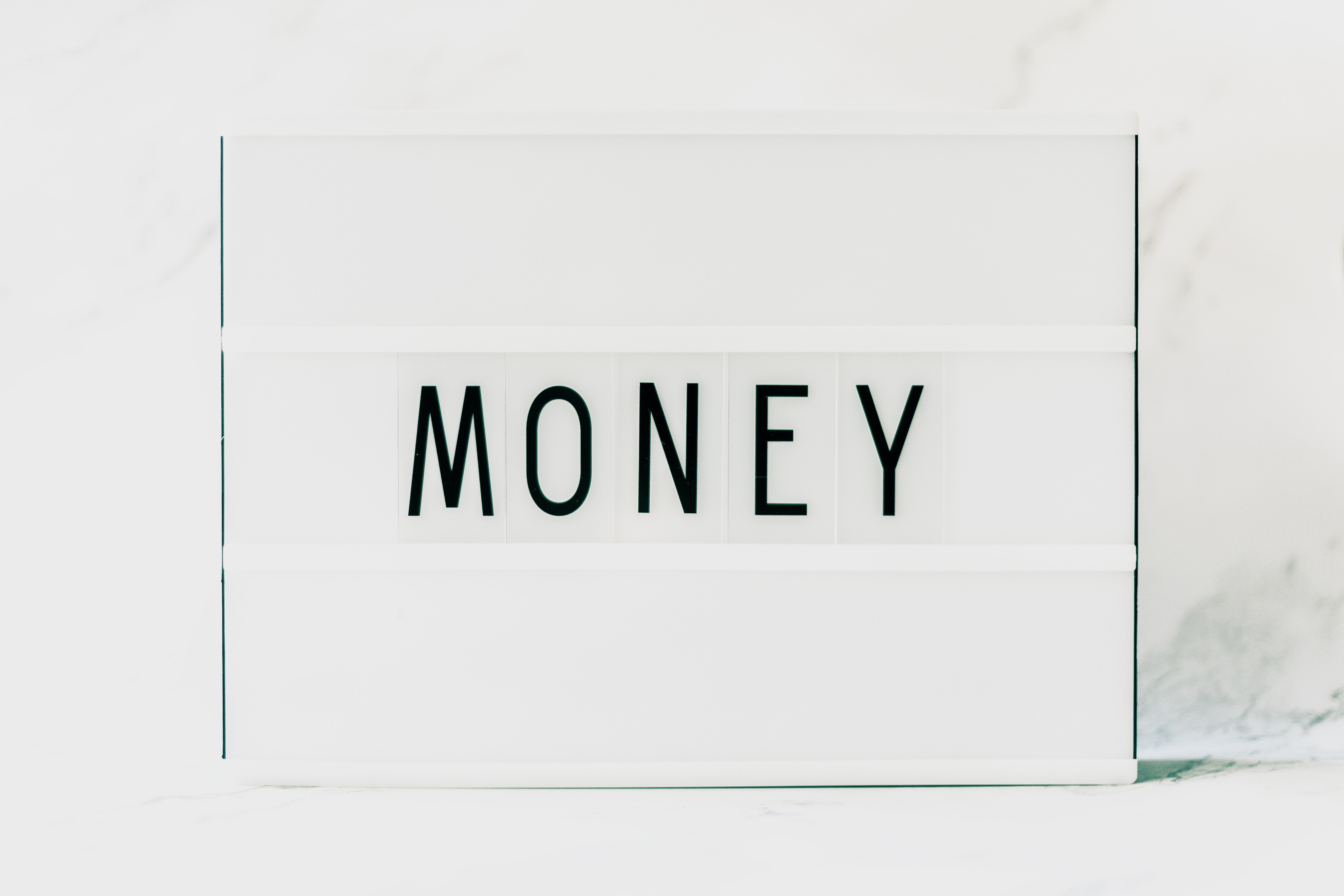 "letter-board with the word ""money"" written on it"