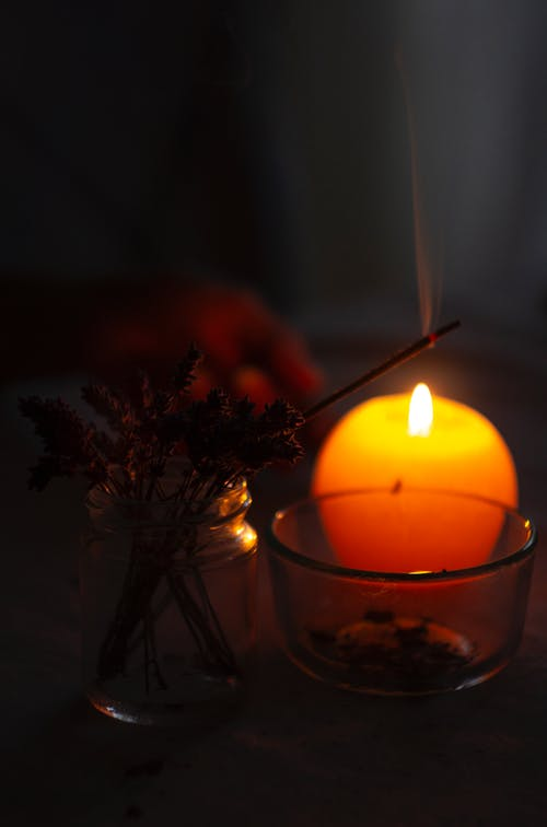 Close-Up Photo of Lighted Incense Stick Near Candle