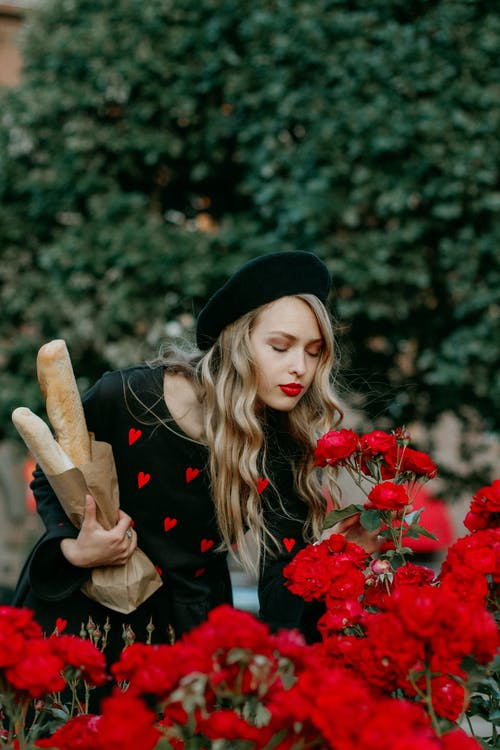 Photo of Woman Holding A Paper Bag Of Bread While Smelling Red Flowers
