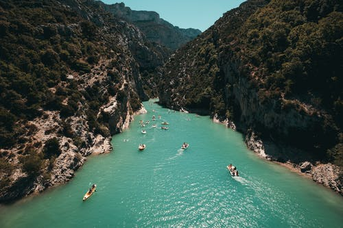 Photo of People Riding Kayaks Near Mountains