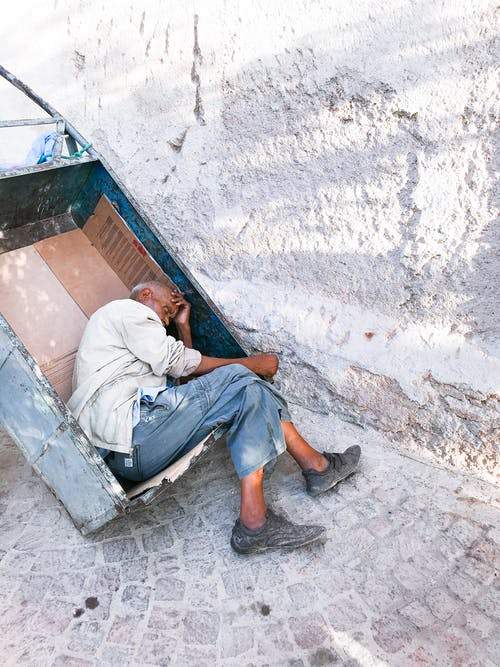An Elderly Man Sleeping On A Metal Cart On The Of A Street Close To A Wall