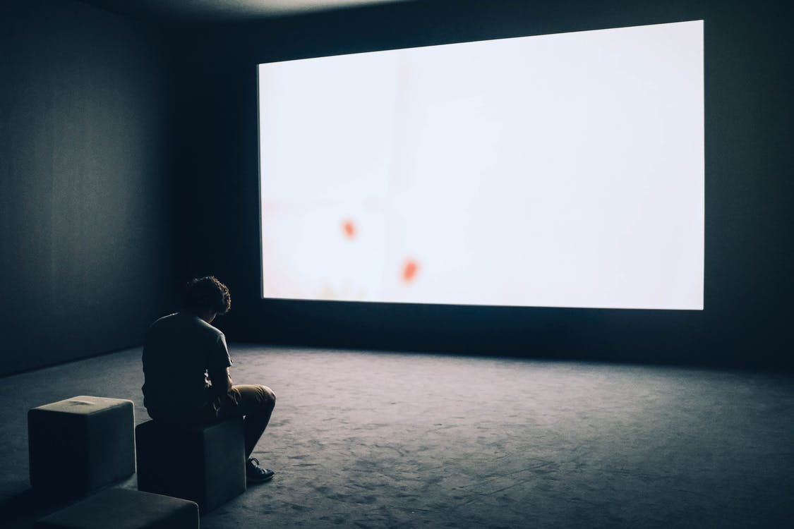 Man Sitting in Front of Turned-on Screen