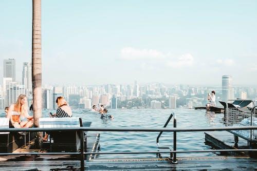 People Beside Pool Near Buildings