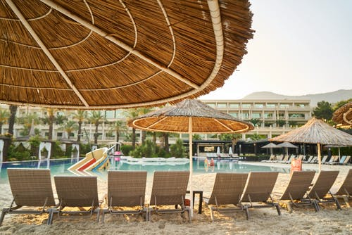 Photo of Sunloungers on Sand Near Swimming Pool