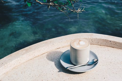 Photo of Coffee Cup Near Body of Water